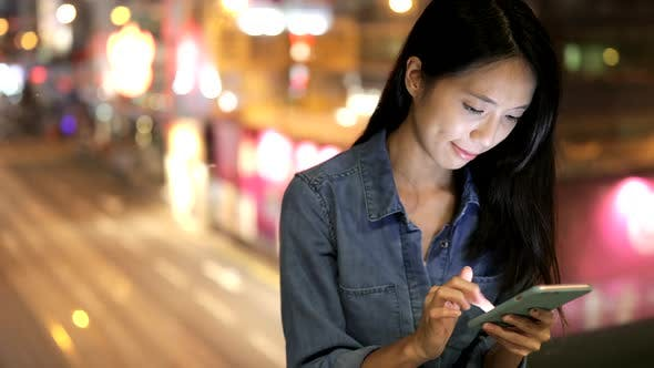 Thumbnail for Woman using cellphone at night