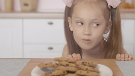 Thumbnail for Cheerful Little Girl Peeking Out of Table and Taking Sweet Tasty Cookie From Plate