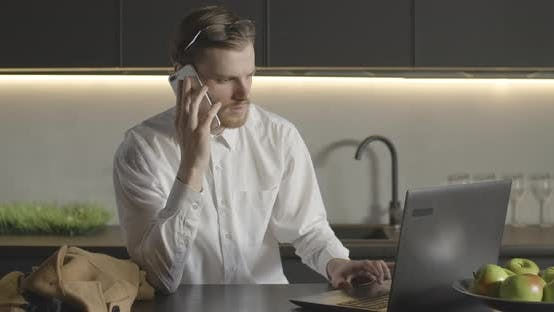 Thumbnail for Slowmo of Busy Caucasian Man Surfing Internet and Talking on the Phone in Kitchen. Portrait of