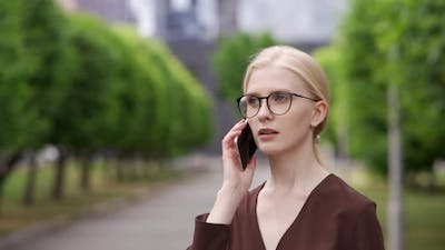 Young Business Woman Answers the Phone and Talks on the Phone with a Colleague at Work