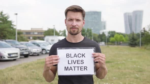 A Young Handsome Caucasian Man Shows a Black Lives Matter Sign To the Camera By a Parking Lot