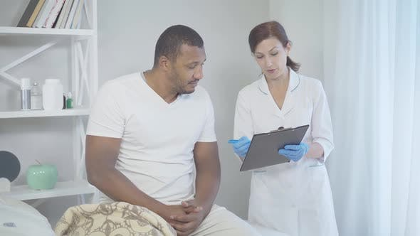 Thumbnail for Mid-adult Caucasian Woman Talking with Man Sitting on Bed in Hospital Ward and Smiling. Portrait of