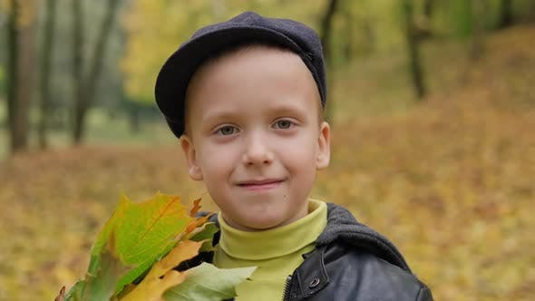 Little Boy in Cap Smiling and Looking at Camera in Autumn Park
