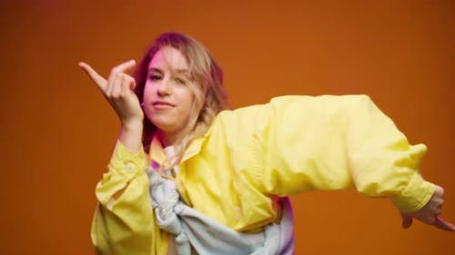 Trendy Young Woman Dacing Against Yellow Background