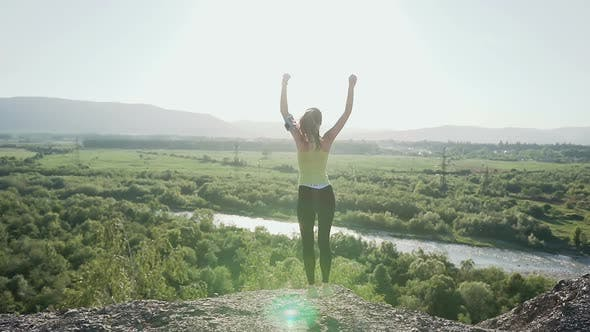 Thumbnail for Young Sports Girl Standing on Top of the High Cliff Above the River