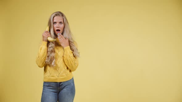 Thumbnail for Woman Holding a Banana Phone Acting Shocked and Then Smiling at the Camera