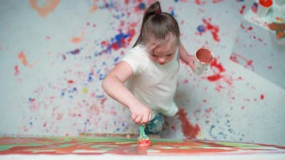 Kid Girl with Down Syndrome Draws with a Brush on a Large Canvas in a White Room Kid Girl with