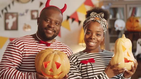 Thumbnail for Cheerful Black Couple Posing with Jack-o-Lanterns on Halloween