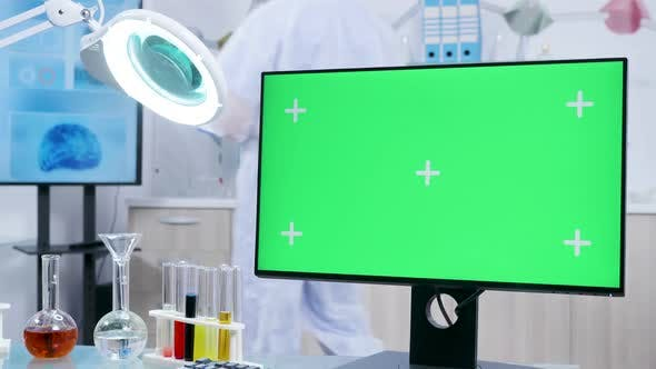 Static Shot of Chemist Desk with a Green Screen Mock-up Desktop PC