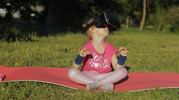 Child in VR Headset Helmet Sitting in Lotus Position on Mat and Performing Yoga Meditation in Park