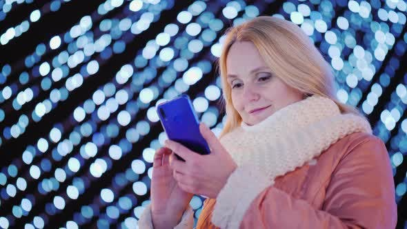 Thumbnail for A Young Woman Uses a Smartphone on the Background of Festive Garlands in the City