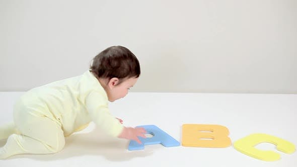 Baby boy playing with toy alphabet blocks