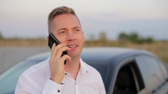 Handsome smiling businessman standing near car and using mobile phone.