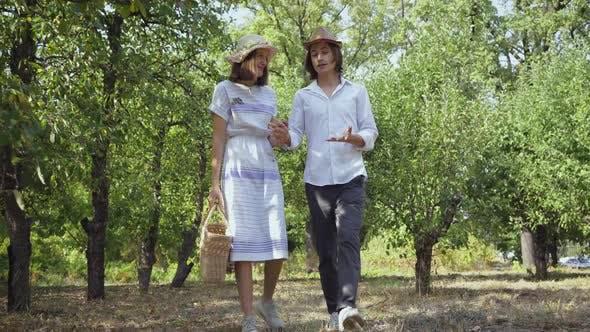 Niedliches Paar, das im Park oder Garten geht, Hände hält, spricht und lächelnd