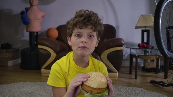 Thumbnail for Face of Caucasian Curly-haired Boy Chewing Hamburger and Watching TV. Cute Teenager with Fast Food