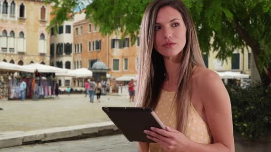 Thumbnail for Friendly Caucasian girl in her 20s using pad device in street in Venice, Italy