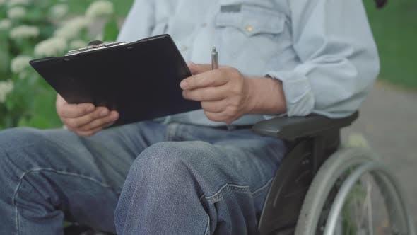 Thumbnail for Unrecognizable Paraplegic Senior Man Signing Documents Outdoors. Old Caucasian Paralyzed Retiree