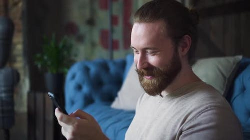 Man Giggling Laughing When Scrolling His Phone
