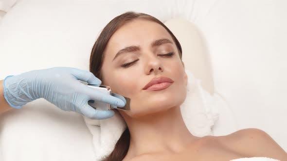 Kosmetiker-Arm mit Kosmetologie-Apparat auf weiblichem Gesicht