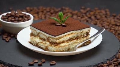 Portion of Traditional Italian Tiramisu dessert and coffee beans