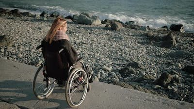Woman with Disabilities Is Sitting in Invalid Carriage and Looking on Sea