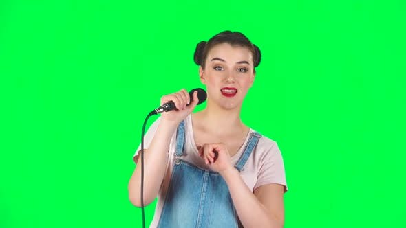 Cover Image for Attractive Girl Sings Into a Microphone and Moves To the Beat of Music, Slow Motion