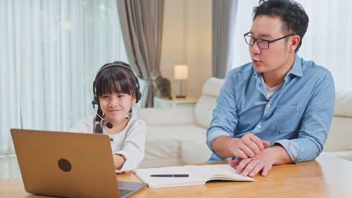 Homeschool Asian little young girl learning online class from school teacher by digital taplet