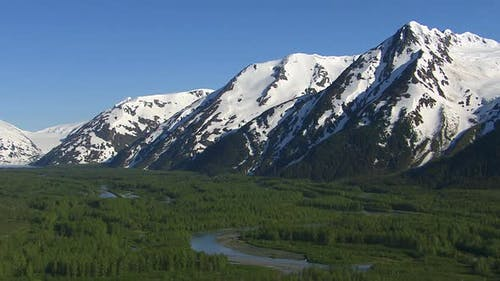 Luftaufnahme von Waldbächen und verschneiten Bergen, Alaska