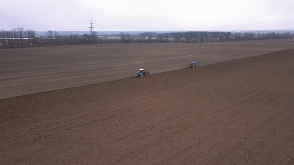 Thumbnail for Agricultural Work in the Field, Two Blue Tractors Plow the Land