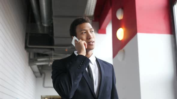 Thumbnail for Walking Businessman Talking on Phone in Office, Happy Mood