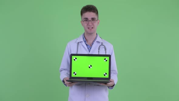 Thumbnail for Happy Young Man Doctor Talking While Showing Laptop