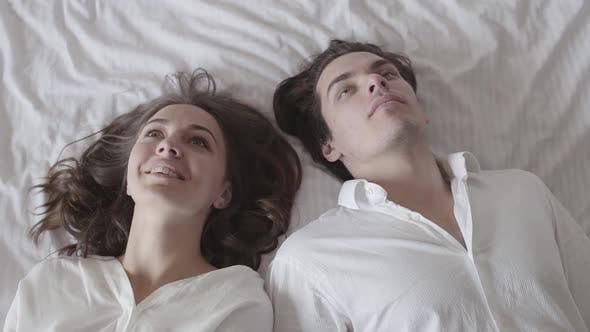 Thumbnail for Happy Man and Woman Falling on the Bed and Looking at Each Other with Love. Young Couple Lying in