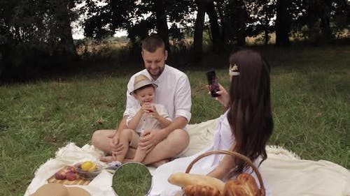 Female Taking Photos of Her Spouse and Son