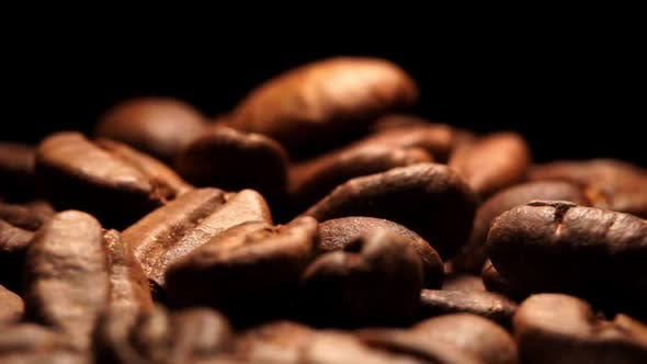 Close up view of fresh roasted Arabica coffee beans on black background drops from above