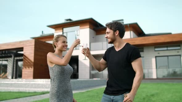 Thumbnail for Romantic Couple Drinking Champagne Near House