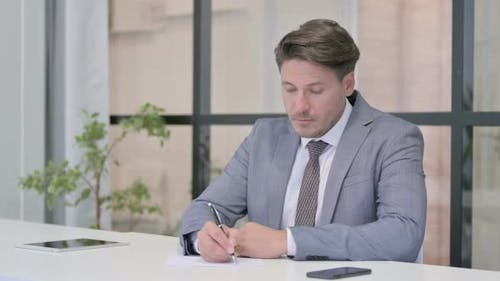 Middle Aged Man Writing on Paper in Office