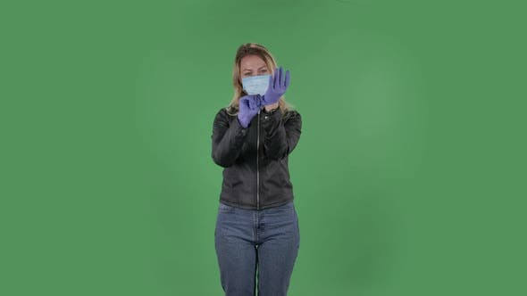 Thumbnail for Portrait of Beautiful Young Woman in Medical Mask Is Looking at Camera and Puts on Rubber Gloves