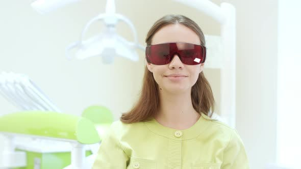 Thumbnail for Female Dentist Dressing Up Ultraviolet Orange Safety Goggles. Woman Doctor