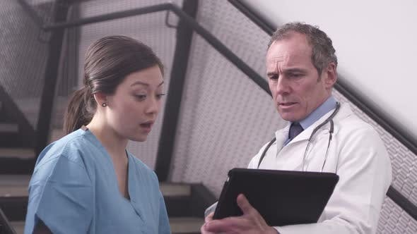 Thumbnail for CU Doctor and nurse using tablet and discussing in hospital / London, United Kingdom.