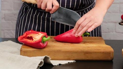 Caucasian woman in blue apron cuts ripe red bell pepper