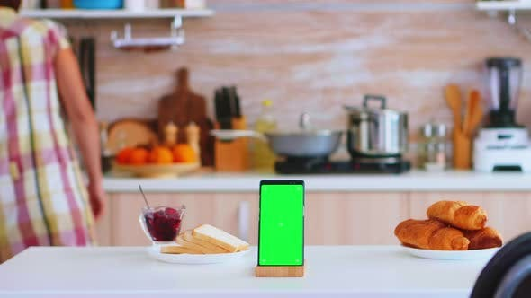 Phone with Green Screen Next To Baked Pastry