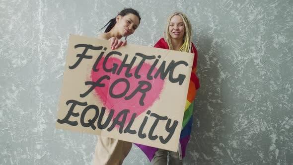 Teenage Girl Hugs and Covers Her Girlfriend with a Rainbow Flag