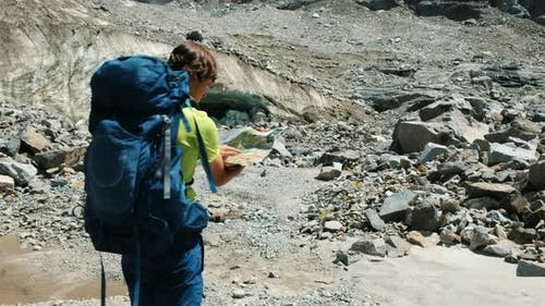 Tourist Man Walks with a Backpack, Studies a Map and Shows a Route in the Mountains Against a Blue