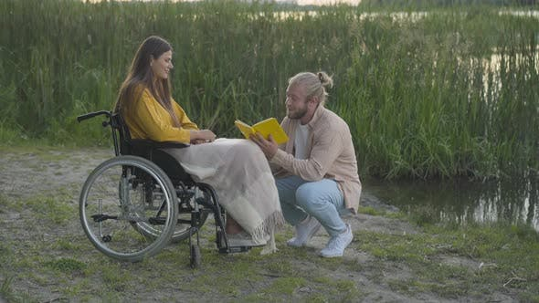 Wide Shot of Loving Caucasian Man Reading for Paralyzed Woman at Sunset on River Bank. Portrait of