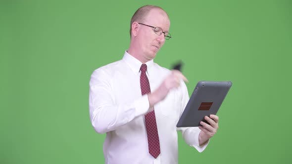 Thumbnail for Happy Mature Bald Businessman Talking on the Phone While Using Digital Tablet