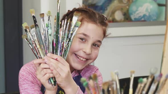 Thumbnail for Cute Happy Girl Smiling To the Camera Holding Bunch of Paintbrushes