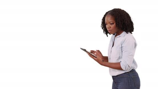 Thumbnail for Attractive black female in shirt and jeans using tablet in studio with copyspace