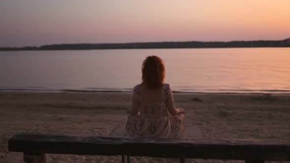Dolly in Young Woman Meditating at River During Sunset