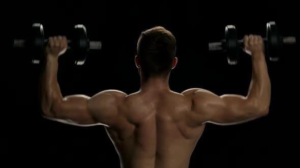 Rear View Muscular Man Lifting Dumbbells.