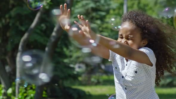Thumbnail for Excited African Girl Enjoying Soap Bubble Show in Park